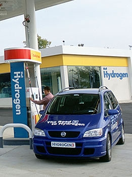 Photo of a blue car with 'The Road to Hydrogen' written on it, filling up at a hydrogen fueling station.