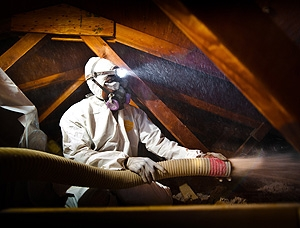 This photo shows a man in a white hazardous materials suit blowing insulation inside of an attic. He is wearing a headlamp on his head and the beam shines in the general direction of the insulation tube he is holding.