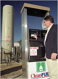 Photo of a man standing next to a propane fuel pump with a tank in the background.