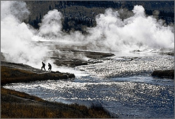 Photo of two men walking away from a natural steam pool.