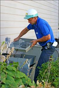 Photo of an HVAC professional performing maintenance on an outdoor air conditioning unit.