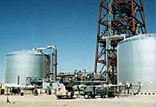 Photo of two large, gray storage system tanks at a power tower plant. The base of the tower can be seen in the background. Pipes leading into and out of the tanks carry heat-transfer fluid.