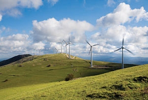 Photo of a hilly field, with six visible wind turbines spinning in the wind.