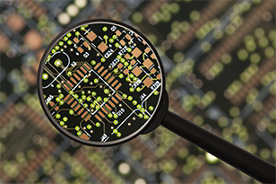 Photo of circuit board under a magnifying glass