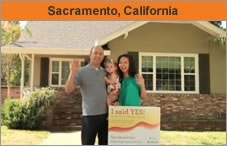 Photo of a family facing the camera, standing in front of a house, the husband with a toddler in his arms. They're in front of a small sign that says 'I said YES!' The headline over the photo reads 'Sacramento, California.'