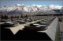Photo of geothermal cooling towers with fans running. Mountains are in the background.