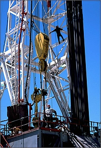 Photo of a well drilling rig. A man stands on the platform while another is climbing the rig.