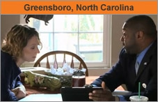 Photo of a man and a woman sitting and talking at a dining room table in a home. The headline over the photo reads 'Greensboro, North Carolina.'