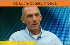 A photo of a man, head and shoulders, facing an interviewer off-camera. The headline over the photo reads 'St. Lucie County, Florida.'