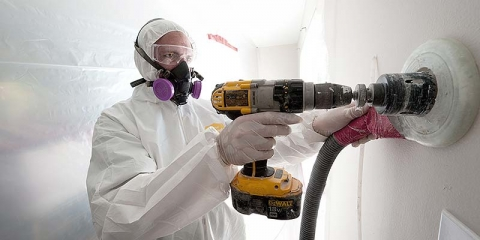 Image of a person with a drill weatherizing a wall.