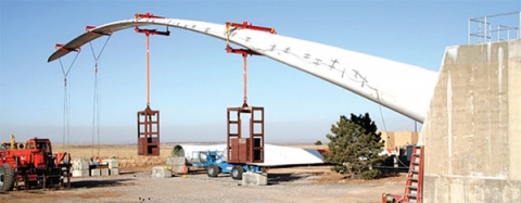 Photo of wind turbine blade being bent by a series of weights hung along its length.