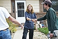 Photo of a woman shaking hands with a weatherization worker, who has his back facing the camera, and both of whom are standing in front of her house.