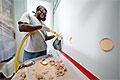 Photo of a man with a respirator and construction dust on his arms installing blown insulation into a wall.