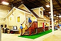 Photo of a small home inside a warehouse with two people standing on a stairway at the entrance.  The home is used to train weatherization workers.
