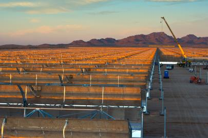 Installing a concentrating solar power system in Gila Bend, Arizona. The curved  mirrors are tilted toward the sun, focusing sunlight on tubes that run the length of the mirrors. The reflected sunlight heats a fluid flowing through the tubes. The hot fluid then is used to boil water in a conventional steam-turbine generator to produce electricity.   Photo by Dennis Schroeder.