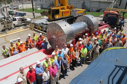 Federal and contractor employees who worked on the project to remove irradiated components from a reactor pool gather to watch the transport of the shipment offsite for disposition.