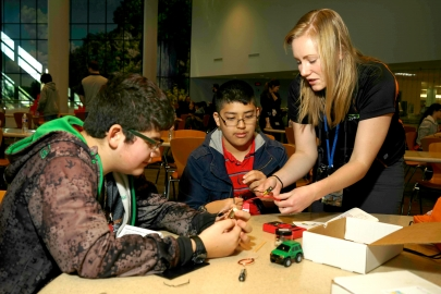 Tori Hawn, communications manager for the Colorado State University team, is showing two of the middle schoolers at Education Day how to put together a regenerative braking kit. Regenerative braking is used in hybrid electric vehicles to capture and reuse energy from the brakes that would be otherwise lost.
