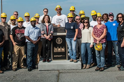 EM Assistant Secretary Monica Regalbuto, directly left of the Tank Closure Monument, gathers with federal and contractor employees at SRS.