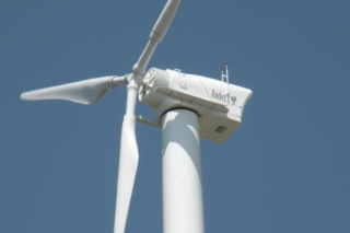 A photo of a wind turbine from the point of view of looking upward at the blades and nacelle.