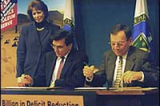Energy Secretary Federico Pena (left) signs the historic transfer agreement.