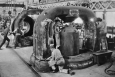 "The cyclotron, invented by Ernest Lawrence in the 1930s, is a unique circular particle accelerator, which Lawrence himself referred to as a ""proton merry-go-round."" In reality, the cyclotron specialized in smashing atoms. Part of this atom-smashing process requires very large, very heavy magnets -- sometimes weighing up to 220 tons. In this photo, workers at the Federal Telegraph facility in Menlo Park, California, are smoothing two castings for 80-ton magnets for use in one of Lawrence's cyclotrons at the University of California, Berkeley. Lawrence passed away in 1958 -- and just 23 days later, the Regents of the University of California voted to rename two of the university's nuclear research sites: Lawrence Livermore and Lawrence Berkeley Laboratories. 