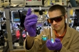 In this photo, Brookhaven scientist Dmitry Polyansky examines a vial containing a specialized catalyst designed to help convert solar energy into fuel. Producing clean-burning hydrogen fuel from just sunlight and water requires custom-built catalysts for water oxidation -- the part of the water-splitting process that generates oxygen atoms. A tiny amount of the solid catalyst, developed in collaboration with the University of Houston, dissolves and turns the water that lovely shade of blue. | Photo courtesy of Brookhaven National Laboratory.