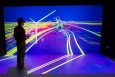 """At the National Renewables Energy Laboratory (NREL), scientists use the Insight Center Collaboration Room to examine and interact with their data. In this simulation, the room is converted into a virtual wind tunnel, allowing scientists to study the complex, turbulent flow fields around wind turbines.   Pictured here, NREL Senior Scientist Kenny Gruchalla examines the velocity field surrounding a wind turbine, using a 3-D model projected onto the center's 16-by-8 foot wall. The simulation helps scientists better understand flow patterns, and further, how turbines can better avoid gearbox failures. <a href=""""http://www.nrel.gov/news/features/feature_detail.cfm/feature_id=2254"""" target=""""_blank"""">Learn more about the Insight Center Collaboration Room</a>.   Photo courtesy of Dennis Schroeder, NREL."""