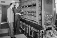 """In this photo, two Argonne researchers are pictured with Argonne's first digital computer, AVIDAC. Designed and built by Argonne's Physics Division for $250,000, it began operations on January 28, 1953. AVIDAC stands for """"Argonne Version of the Institute's Digital Automatic Computer"""" and was based on architecture developed by mathematician John von Neumann. Groundbreaking as it was, today's smartphones are far more sophisticated and powerful than this machine. 
