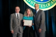 Sue Reilly, President of Group14 Engineering, Inc., accepted the award for DOE Protege of the Year at the Small Business Forum & Expo from Kevin Knobloch, DOE Chief of Staff (l), and John Hale III, Director of DOE's Office of Small and Disadvantaged Business Utilization (r) at the Small Business Forum & Expo, Tampa, FL, on July 12, 2014