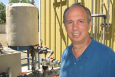 Pictured here is Michael Brambley in front of equipment that supplies chilled water to PNNL Building Diagnostics Laboratory's air handler. The cooled air from an air handler is distributed to terminal boxes, which are the last point for controlling air temperature and flow before distributing it throughout a building zone. In a new control strategy for commercial buildings, the terminal boxes would process the information collected by occupancy sensors to control the air handler's fan speed for energy savings.   Photo courtesy of Kristin Nolan, freelancer.