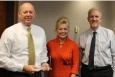 "EMCBC Director Jack Craig, left to right, EM Executive Assistant Jillian Carter, who is EM's Feds Feed Families representative, and Senior Advisor for Environmental Management David Huizenga pause for a photo Nov. 8. Craig holds the ""Teamwork Award"" he and his staff received."