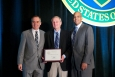 Charles Kolb of Aerodyne Research Inc. accepts the SBIR/STTR Business of the Year Award from Kevin Knobloch, DOE Chief of Staff (l), and John Hale III, Director of DOE's Office of Small and Disadvantaged Business Utilization (r) at the Small Business Forum & Expo, Tampa, FL, on July 12, 2014