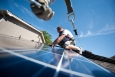 Brian Webster installs rooftop solar panels on a home in Englewood, Colorado. The Energy Department is working to streamline rooftop solar installations so that its faster, easier and cheaper for Americans to go solar. | Photo courtesy of Dennis Schroeder, NREL.
