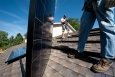 Brian Webster (left) and Mario Richard install photovoltaic modules on an Englewood, Colorado, home. | Photo by Dennis Schroeder, NREL.