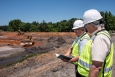 SRNS environmental engineers Ron Socha (left) and Frank Sappington inspect earth-moving work within a basin containing coal ash.