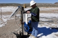 A field technician downloads data from a groundwater characterization well located on Pahute Mesa in the northwestern portion of the NNSS.