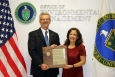 Savannah River National Laboratory Director Dr. Terry Michalski, left, holds his award with EM Associate Principal Deputy Assistant Secretary Monica Regalbuto at EM headquarters.