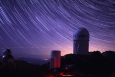 Star trails take shape around Kitt Peak National Observatory in this long-exposure image. The 4-meter Mayall telescope building, at right, now houses Mosaic-3, a new infrared camera built by a collaboration that includes Berkeley Lab scientists. | Photo credit: P. Marenfeld and NOAO/AURA/NSF.