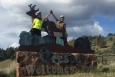 """Rachel Woods-Robinson and Elizabeth Case, the ladies of Cycle for Science, high-five on top of the """"Welcome to Oregon"""" sign. 