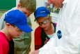 David Curry (far right) teaches Ayden Mowery, Jake Miller, and Bella Presson (left to right) at Ballard County Middle School to read a pH strip to test water.