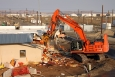 Workers demolish support buildings surrounding the Plutonium Finishing Plant to create a cleared area for heavy equipment to demolish the plant's main processing buildings.