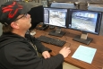 Ron Holm, a RWMC foreman, remotely monitors activities inside an enclosed area where a debris repackaging project is underway.
