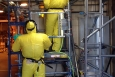 Pipefitters don cooling vests under protective suits in near 100-degree heat inside a building at SRS.