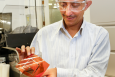 ORNL researchers are experimenting with additive roll-to-roll manufacturing techniques to develop low-cost wireless sensors. ORNL's Pooran Joshi shows how the process enables electronics components to be printed on flexible plastic substrates. Credit: Oak Ridge National Lab