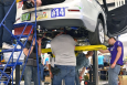 The University of Washington team works on their vehicle while lifted on a hoist. Teams are working in a garage that is fully equipped with tools that will help them make the most of their time this week.   Photo courtesy of EcoCAR 2.
