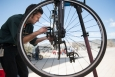 Energy Department employee Bill Vandermeer tunes a bicycle as part of Earth Day events at National Renewable Energy Laboratory last year. Biking to work can help you reduce carbon emissions and save money. | Photo by Dennis Schroeder, National Renewable Energy Laboratory.