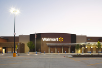Photo of a Walmart store front with an LED parking lot luminaire at left.