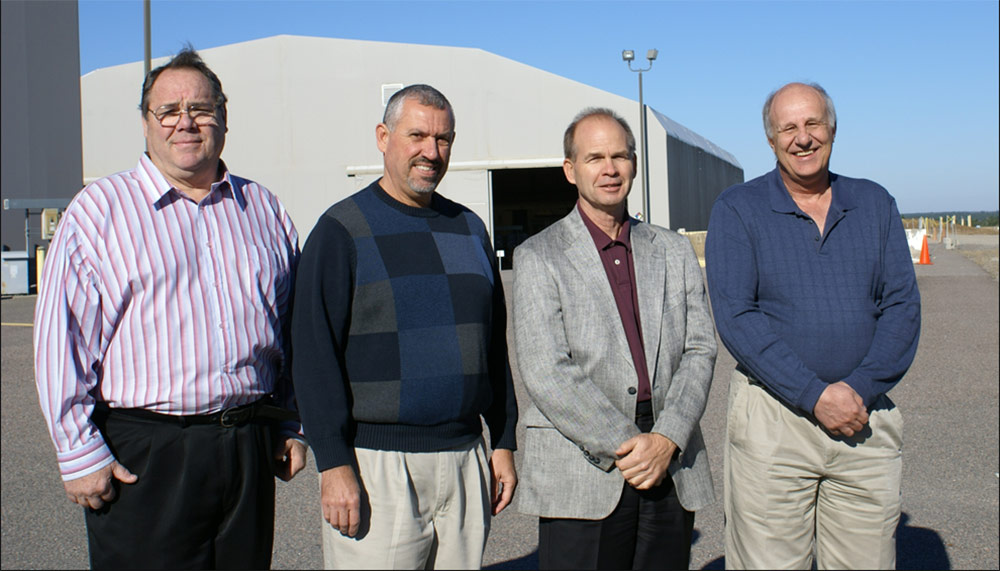 Photo of four men standing outside on a clear blue sky day. There are large gray hanger buildings in the background.