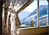 Photo of a window with the curtains open. Sun is shining into the room and snow-covered mountains are visible outside. Copyright iStockphoto.com/Giorgio Fochesato.